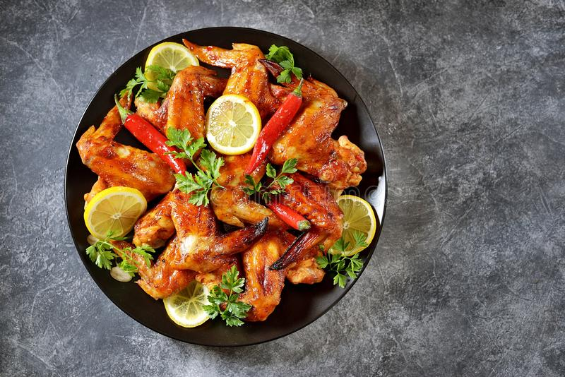 Asas de galinha grelhadas deliciosas com suco de lim?o e pimenta de piment?o no fundo concreto cinzento Vista superior Copie o cp fotos de stock