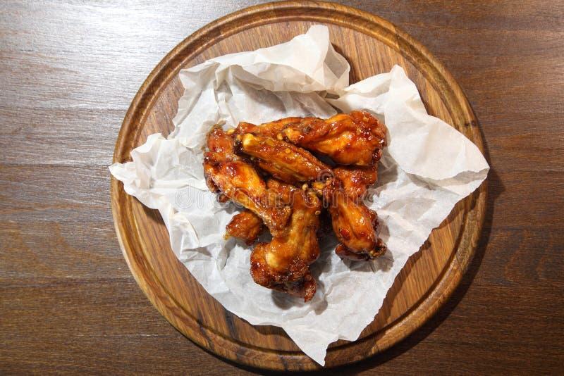 Asas de galinha no molho picante, preparado especialmente para a cerveja Asas de galinha no molho picante em uma placa de madeira imagens de stock