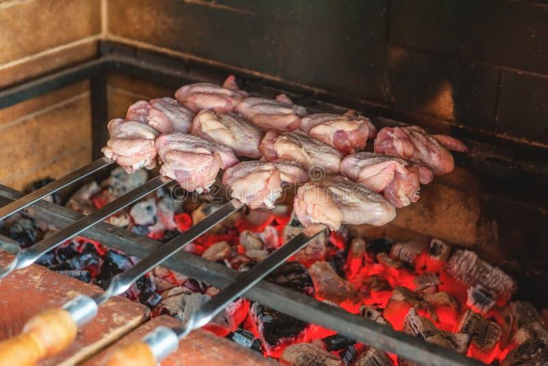 Asas de galinha postas de conserva, cozido no forno em uma grade do carvão vegetal em um dia de verão fotos de stock