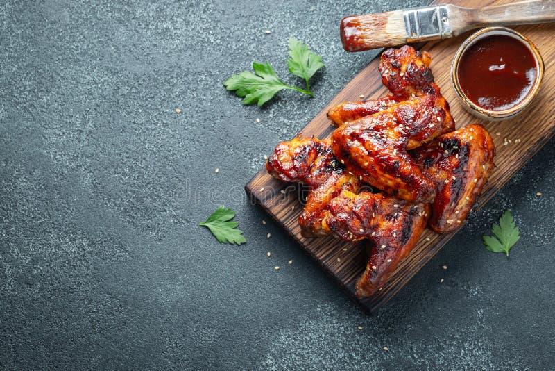 Asas de galinha Roasted no molho de assado com sementes e salsa de sésamo em uma placa de madeira em uma tabela concreta Vista su fotografia de stock royalty free