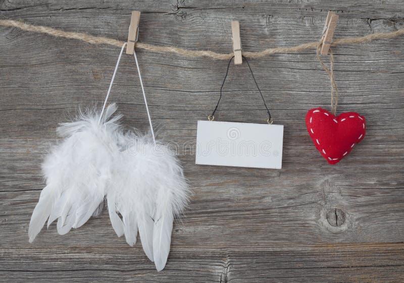 Asas do anjo com coração e nota em branco fotografia de stock royalty free