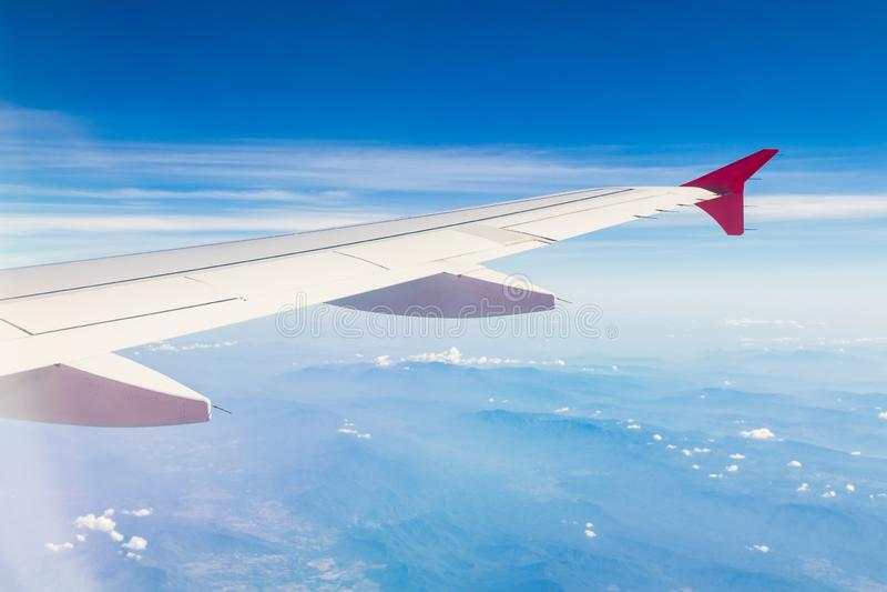 Asas do avião nas nuvens e no céu na montanha, vista da janela plana fotos de stock