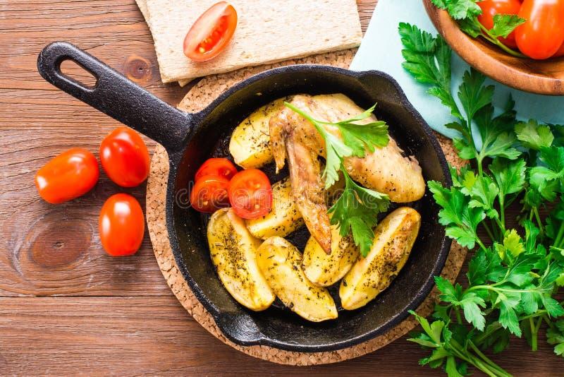 Asas e batatas cozidas de galinha imagem de stock
