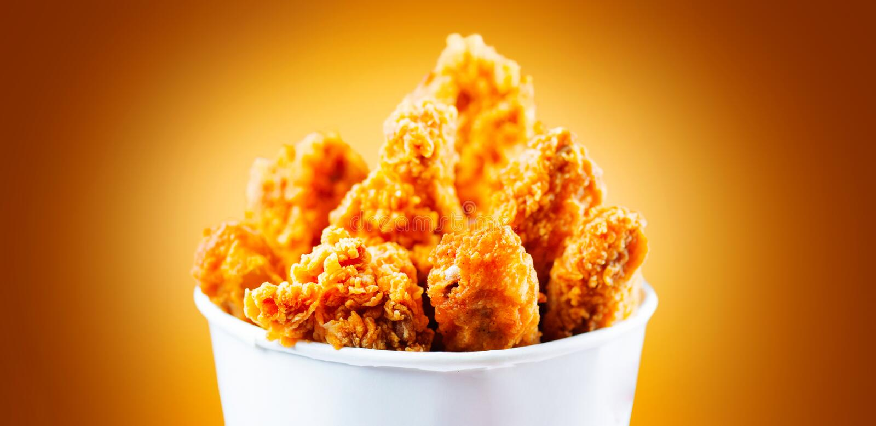 Asas e pés de frango frito Cubeta do frango frito friável de kentucky foto de stock