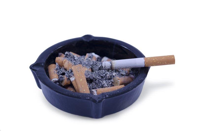 Asbakje met geïsoleerde die sigaretuiteinden en as wordt gevuld, royalty-vrije stock foto