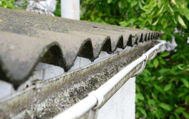 Asbestdak met dakgoot goot het schoonmaken stock afbeeldingen