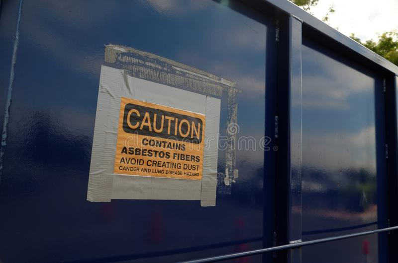Asbestos abatement warning sign. Warning sign on the side of a dumpster outside a demolition site where esbestos abatement is being preformed to remove hazardous stock photo