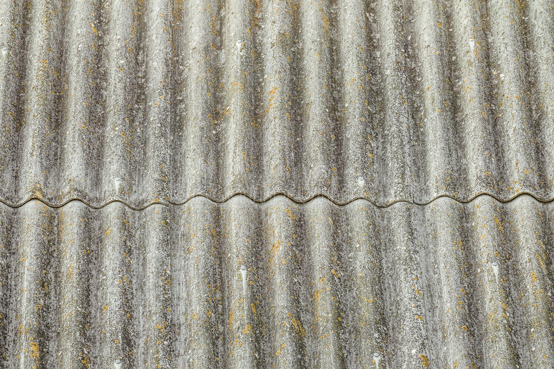 Asbestos cement sheets. Texture of old laid roofing sheets. Grey roof tiles stock image