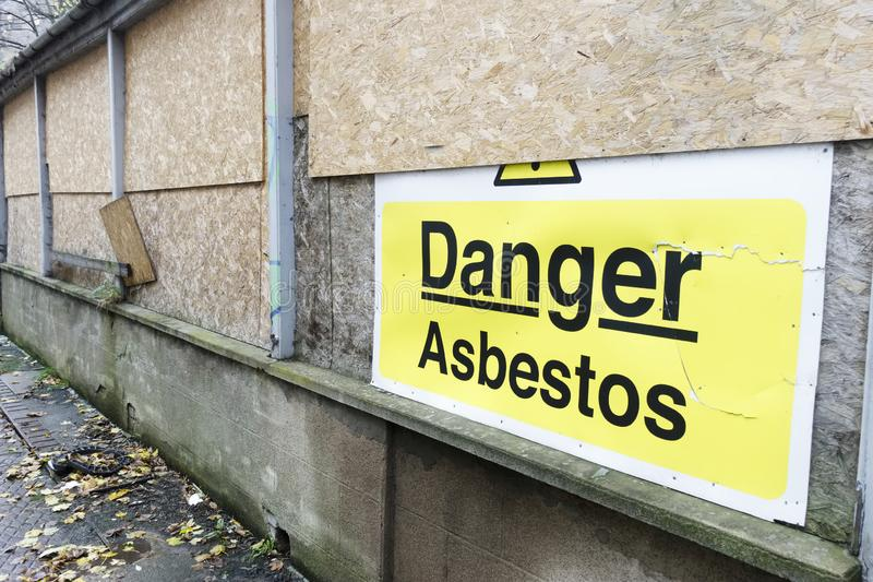 Asbestos danger sign at building construction site refurbishment of old building royalty free stock photography