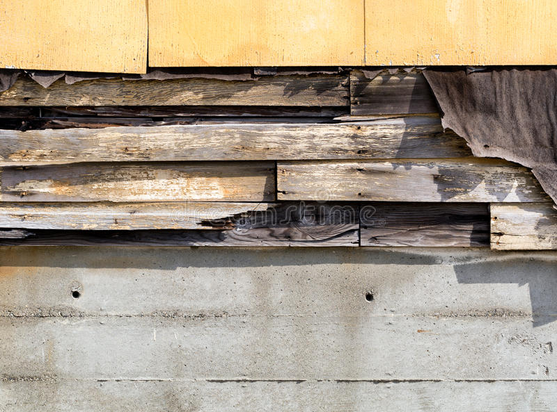 Asbestos siding falling apart due to age. Asbestos siding falling apart with exposed wood and felt underneath royalty free stock images