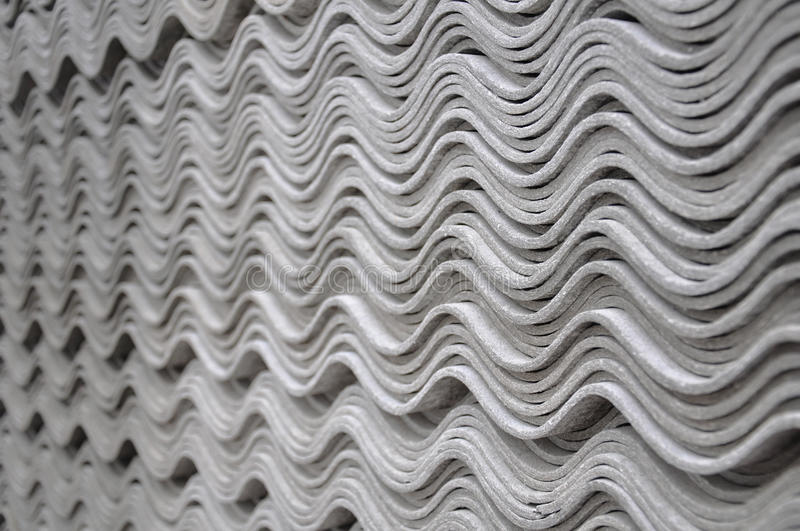 Asbestos tiles - wave pattern. A stack of gray asbestos tiles are forming the wave pattern (movement stock image