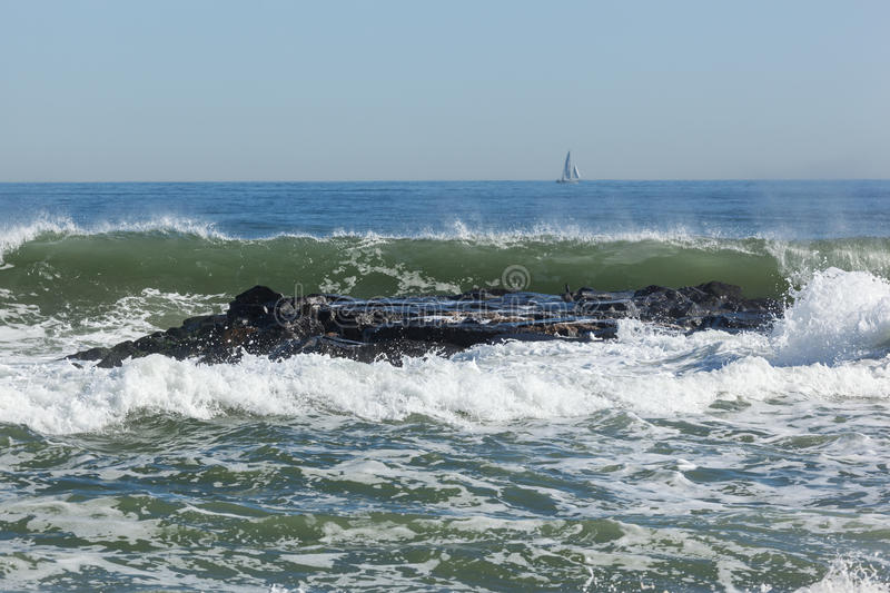 Asbury Park Beach. Waves crash over the jetty in Asbury Park, New Jersey on a crisp fall day stock photography