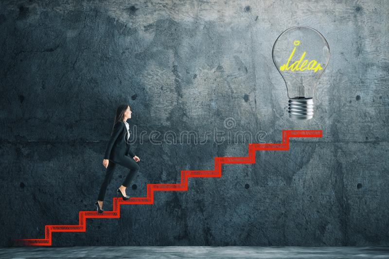 Ascend and innovation concept. Side view of young businesswoman climbing abstract drawn stairs with idea lamp on concrete background. Ascend and innovation stock photo
