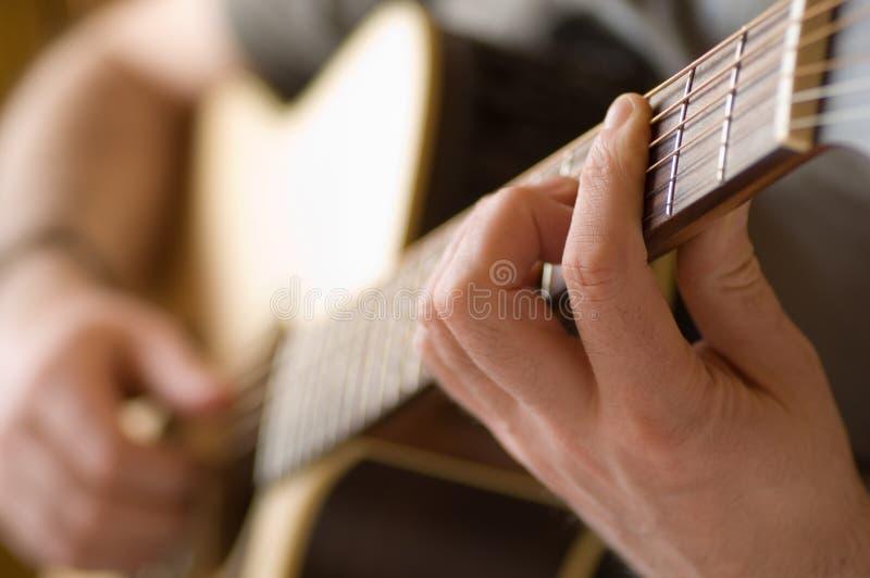 Ascendente cercano de la guitarra que es jugado imagen de archivo libre de regalías