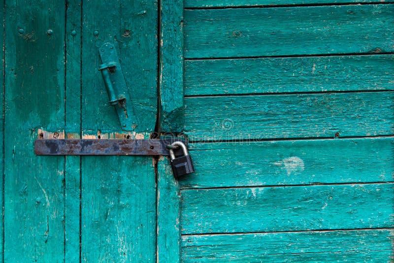 Ascendente fechado da porta velha Pintura brilhante da casca de turquesa Construção de madeira velha fotografia de stock