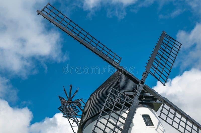 Ascendente próximo do moinho de vento, com velas pretas e o céu azul foto de stock royalty free