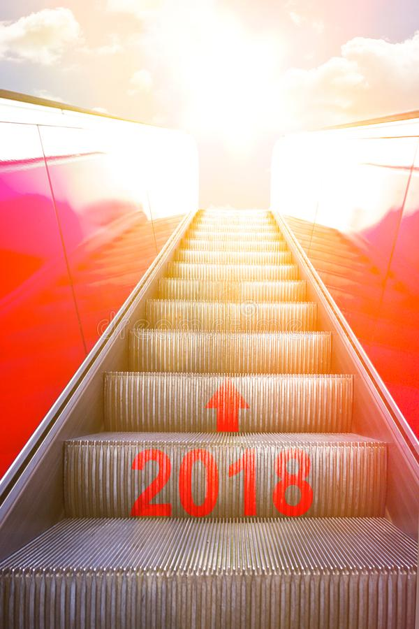 Escalator bright sun light 2018. Ascending on an escalator with an arrow and 2018 written on it into sunlight. Concept photo for a successful new year and a stock photos