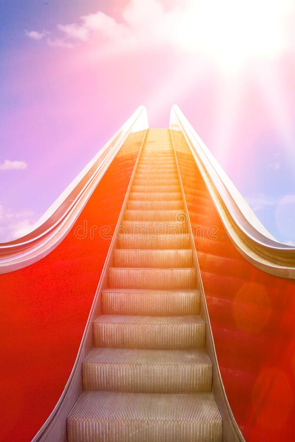 Escalator up bright sun light. Ascending on a moving stairway or escalator into sunlight. Concept photo for success and a bright future royalty free stock photos