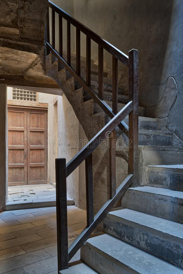 Ascending staircase with wooden balustrade and wooden closed ornate door at the background royalty free stock photos