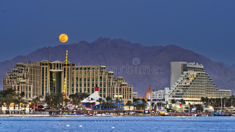 Ascensão colorida da lua na cidade de Eilat, Israel imagem de stock