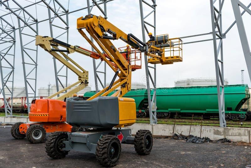 Ascenseur avec le travail de plate-forme dans le domaine de construction de hangar d'entrepôt image libre de droits