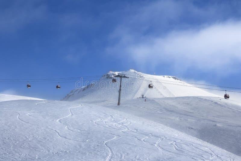 Ascenseur de gondole et pente hors-piste de ski en brouillard à la soirée ensoleillée agréable  photos libres de droits
