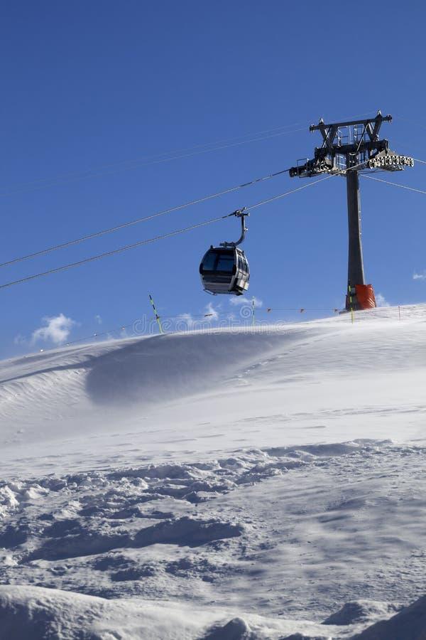 Ascenseur de gondole sur la station de sports d'hiver au jour venteux du soleil images stock