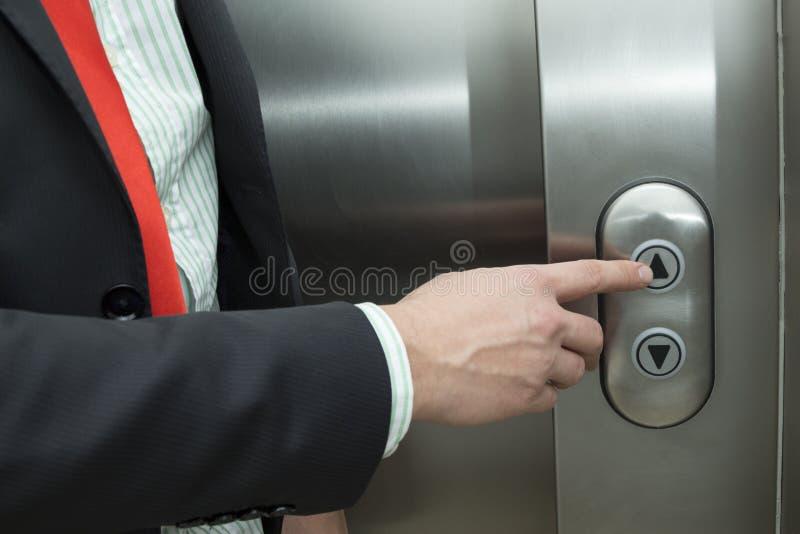 Ascenseur de pressing d'homme d'affaires vers le haut de bouton image stock