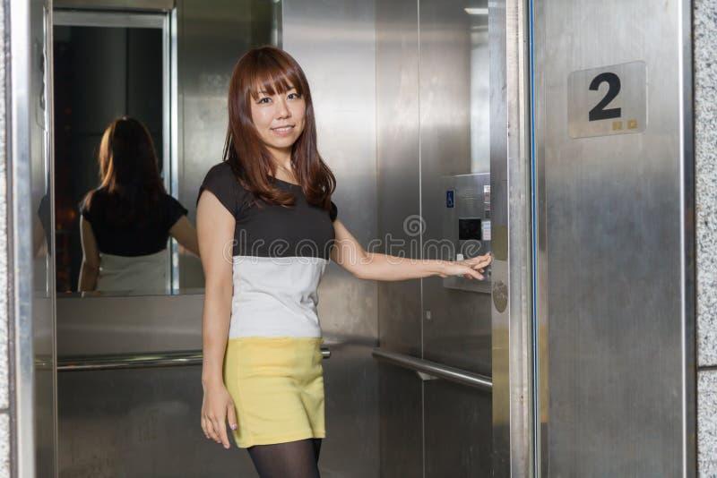 Ascenseur se tenant prêt de belle femme asiatique image libre de droits
