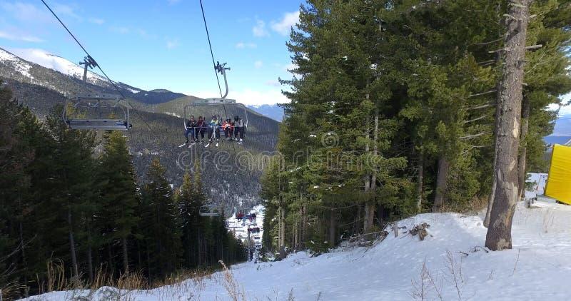 Ascensore di giro di Skiiers fino alla cima della montagna il giorno soleggiato immagini stock libere da diritti
