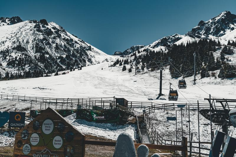 Ascensore di sci di Almaty, il Kazakistan, cabina della cabina di funivia a Medeo all'itinerario di Shymbulak contro il fondo del fotografie stock