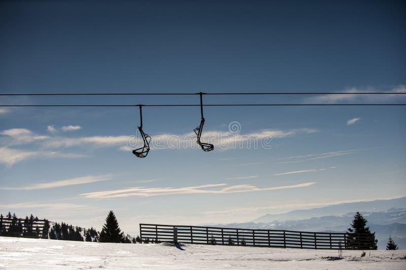 Ascensore di sci con i sedili che superano la montagna fotografie stock libere da diritti