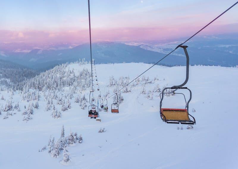 Ascensore di sci con i sedili che superano la montagna ed i percorsi dai cieli immagine stock libera da diritti