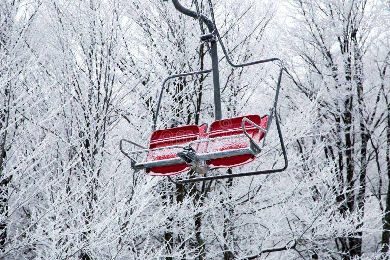 Ascensore di sci con i sedili che superano la montagna ed i percorsi dai cieli fotografie stock
