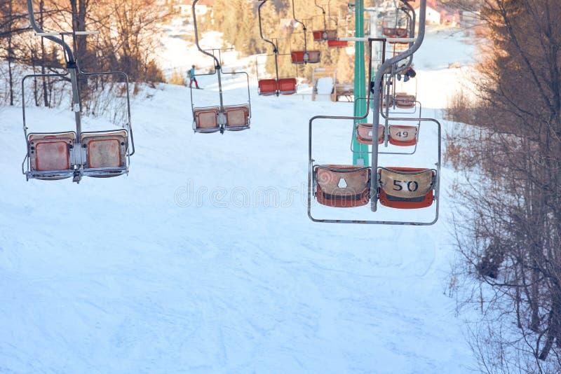 Ascensore di sci con i sedili che superano la montagna fotografia stock