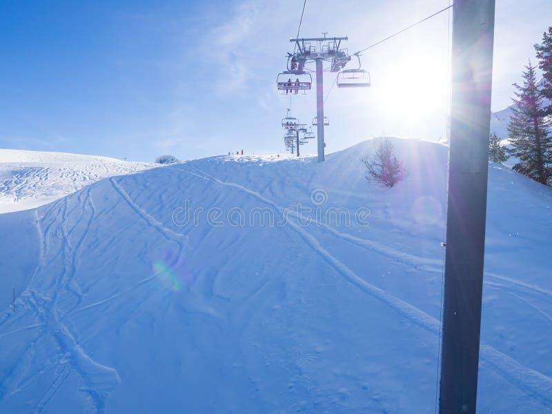 Ascensore di sci con i sedili che superano la montagna ed i percorsi dai cieli e dagli snowboard La Francia, Meribel, 2018 fotografia stock