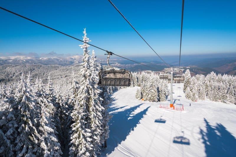 Ascensore di sci con i sedili che superano la montagna sopra le piste dello sci fotografia stock
