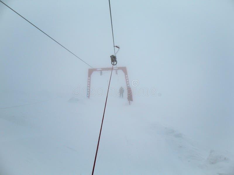Ascensore di sci ghiacciato con lo sciatore inesperto dentro in nebbia spessa Sciatori nella nebbia su una montagna nevosa fotografia stock