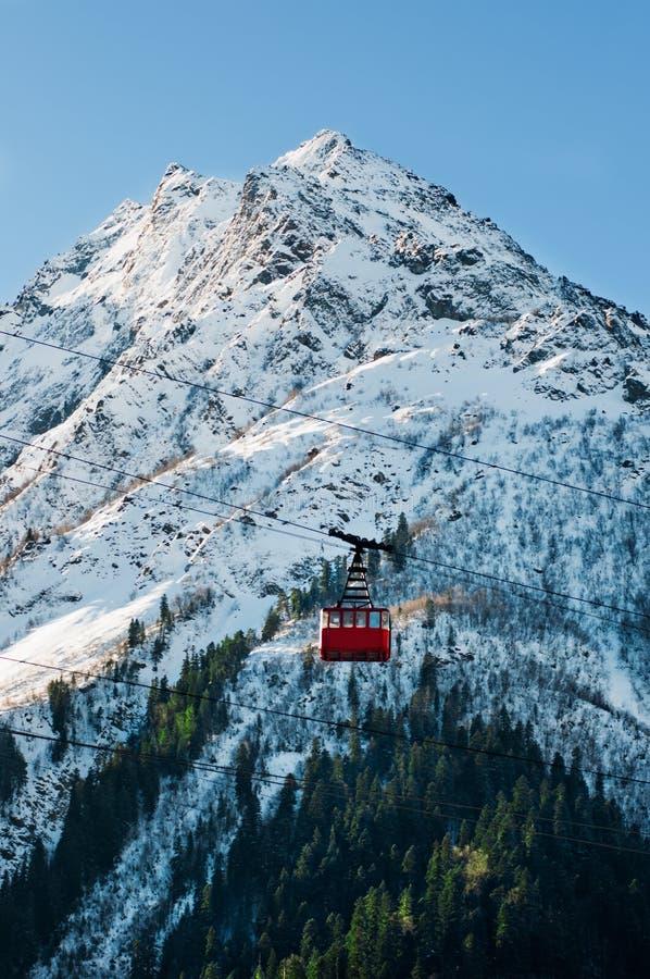 Ascensore ferroviario della cabina di funivia rossa alla stazione sciistica Scelta bianca delle montagne con il fondo del cielo b fotografie stock libere da diritti