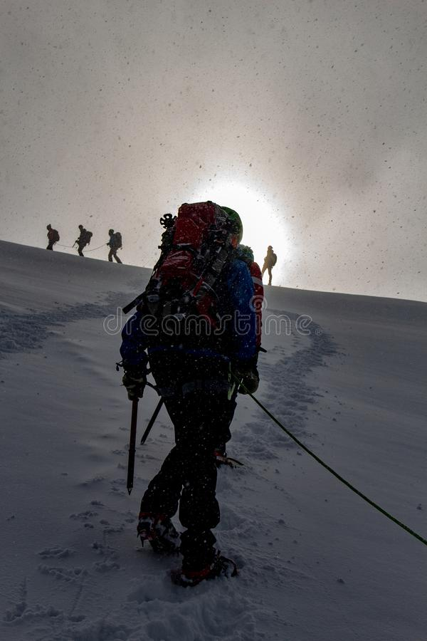 Mountaineer in sunrise on a snowy ascent on a alpine tour called Spaghetti Round in the European Alps, Monte Rosa Massif, Italy. Ascent on a alpine tour called royalty free stock image