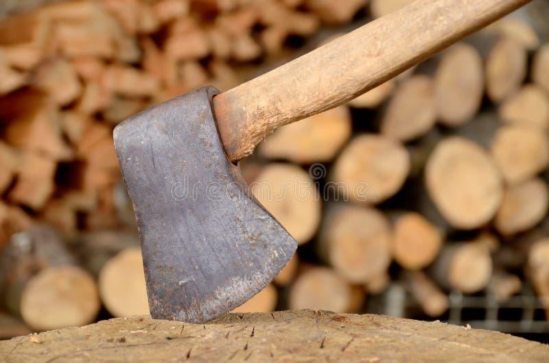 Ascia attaccata nel tronco e nella legna da ardere immagine stock