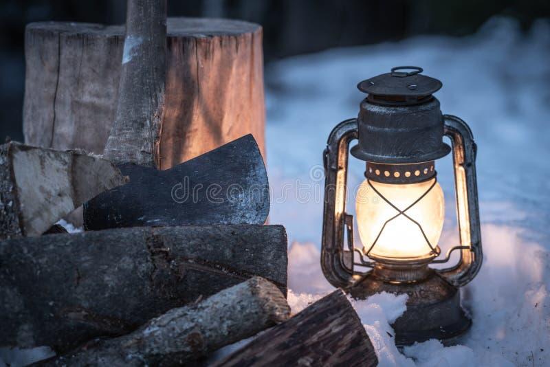 Ascia, legna da ardere e lanterna nella regione selvaggia fotografia stock