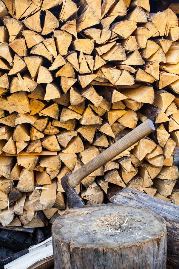 Ascia in un ceppo vicino alla pila di legna da ardere immagini stock