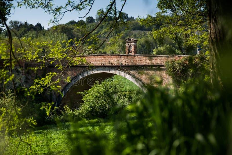 ASCIANO, TOSCANA, Italia - il ponte di Garbo sopra il Ombrone rive fotografie stock libere da diritti