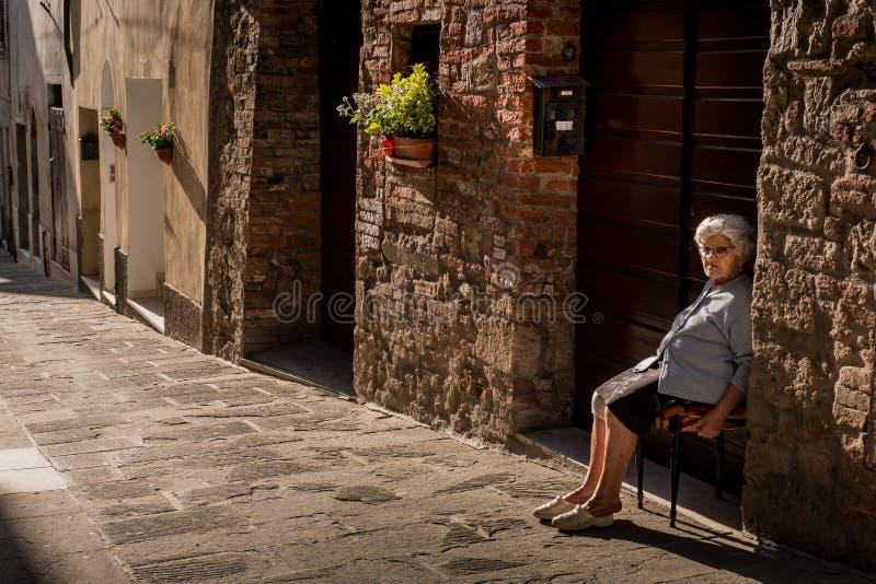 ASCIANO, TOSCANA, Italia - la mujer desconocida se sienta delante de su hom imágenes de archivo libres de regalías