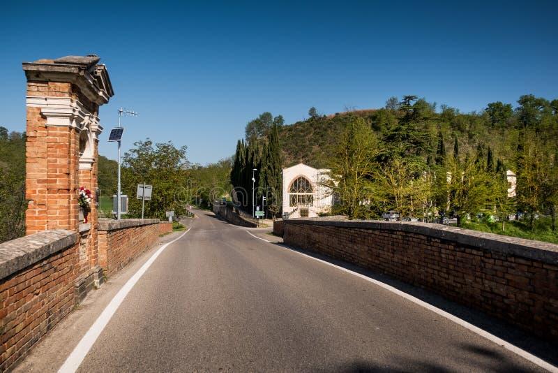 ASCIANO TUSCANY, Italien - den Garbo bron över Ombronen rive royaltyfri bild
