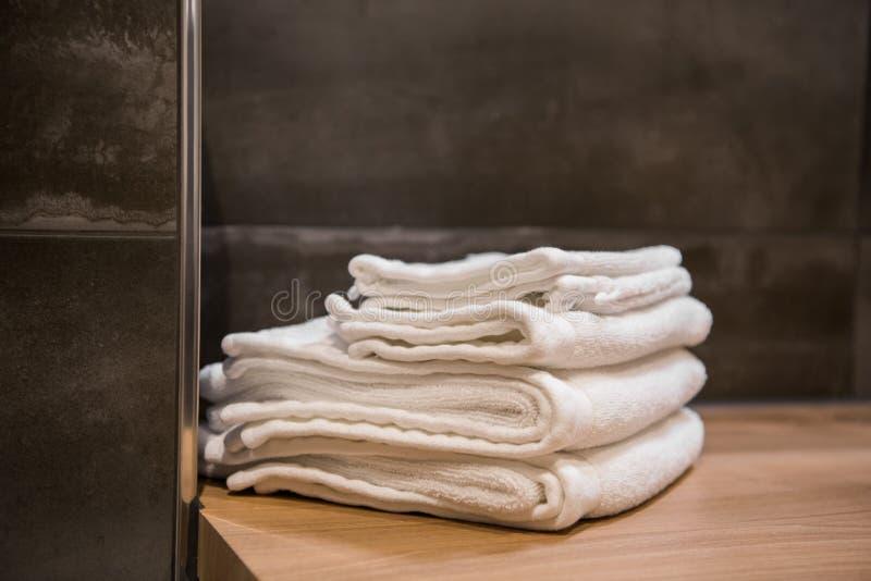 Asciugamani bianchi impilati della stazione termale sulla tavola di legno al bagno moderno immagini stock