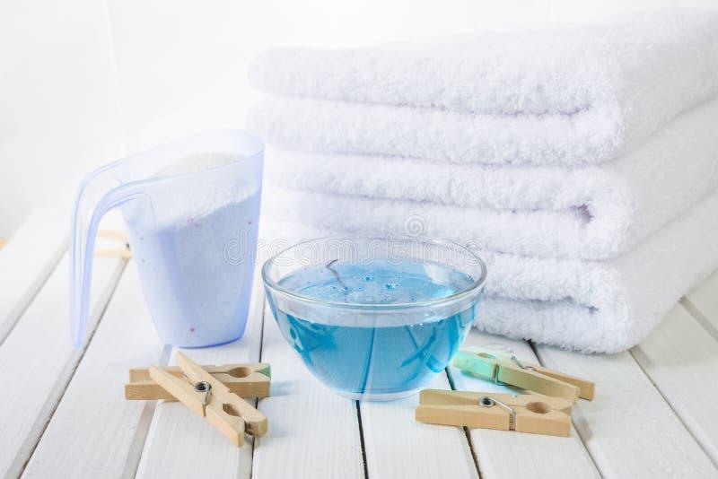 Asciugamani di bagno, detersivo, emolliente del tessuto e clothesp di legno fotografia stock libera da diritti