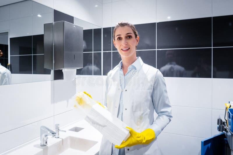 Asciugamani di carta cambianti della donna del portiere in toilette pubblica immagini stock