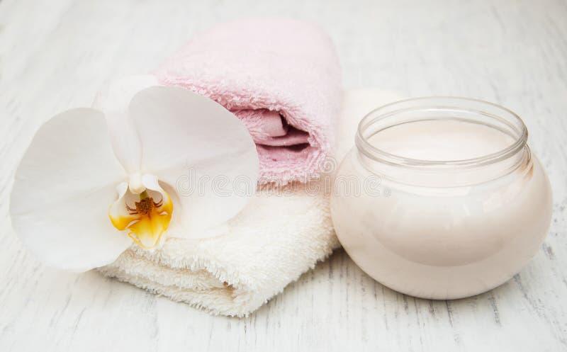 Asciugamani ed orchidee bianchi della crema degli elementi essenziali della stazione termale immagine stock libera da diritti